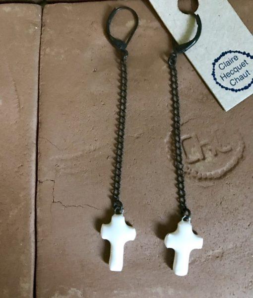 Boucles d'oreilles formée d'une croix en céramique suspendue à une longue chaine sombre.