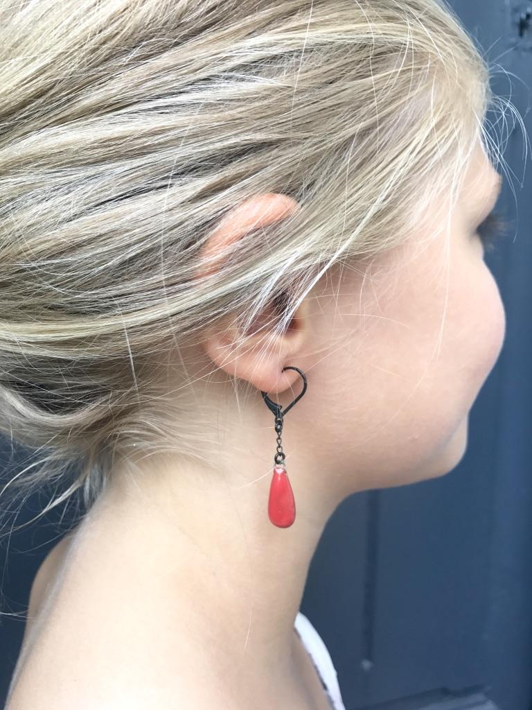 Les boucles d'oreilles Joséphine portées en rouge fort.
