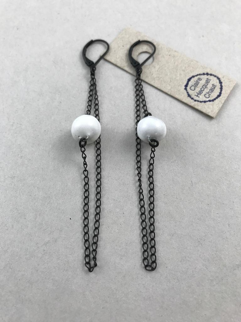 Boucles d'oreilles formées d'un petit pois en céramique suspendu au milieu d'une chaine fine et sombre