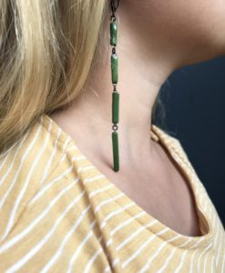 Graphic earrings as a set of thin emerald green rectangular ceramic elements