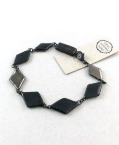 Bracelet sobre et chic formé de losanges noir et platine en céramique liés les uns aux autres.