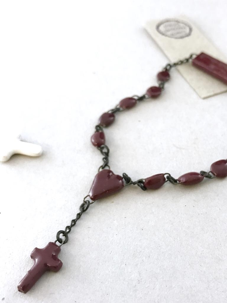 Bracelet de céramique aux perles miniatures, une mini croix de même matière est accrochée par un sacré coeur au bracelet.