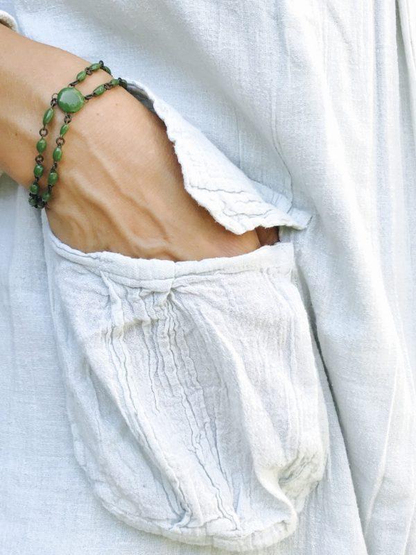 Un bracelet en céramique très fin, formé de deux rangs réunis par une mini perle plate, signature estampillée sur une pampille, fait main en France.