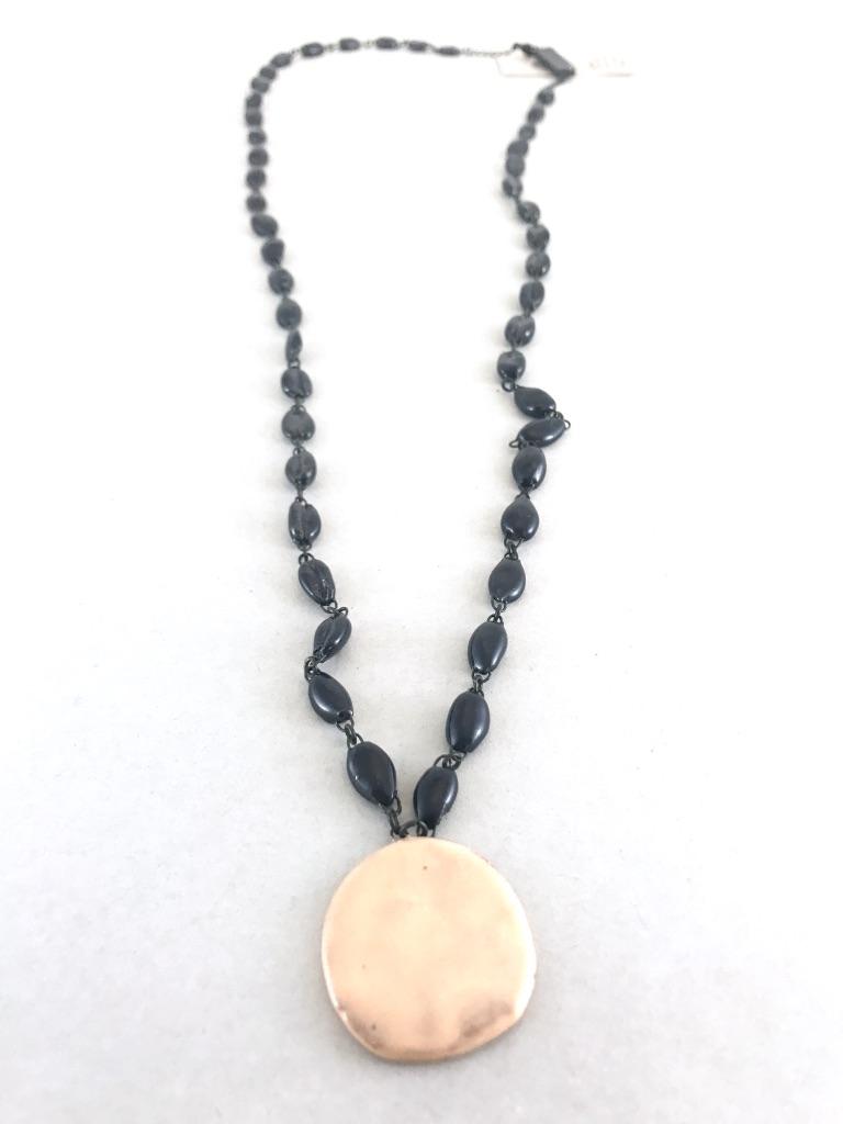 Collier mi long en céramique formé de perles en forme de cauris en faience et terminé par une pastille de même matière.