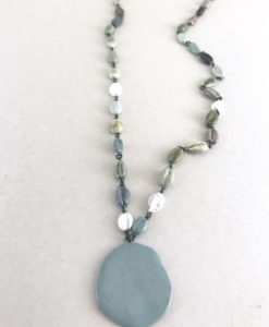 Collier mi long en céramique formé de perles en formé de cauris en faience et terminé par une pastille de meme matière.