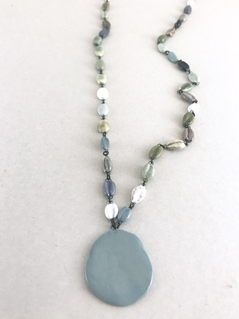 Mid length ceramic necklace made of cowrie shaped beads, in beautiful faded grey. Made in France