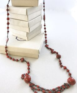 A ceramic chain made of small marbles like beads alternated with clin d'oeil details and ended by three beads lines