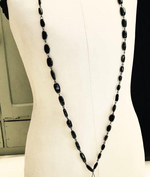 Sautoir long simple et chic formé de perles en céramique noires ou blanches et de deux cerises or ou rouge, fait main en France par Claire Hecquet-Chaut