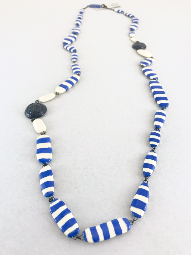 Un sautoir en céramique qui reprend les codes de la marinière, rayure et motif ancre, un bijou excentrique et chic
