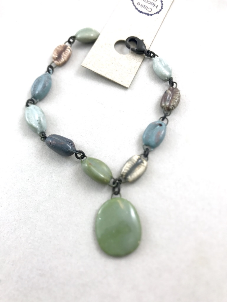 Bracelet en céramique fine made in France fait de cauris émaillés en couleurs gris transparents.